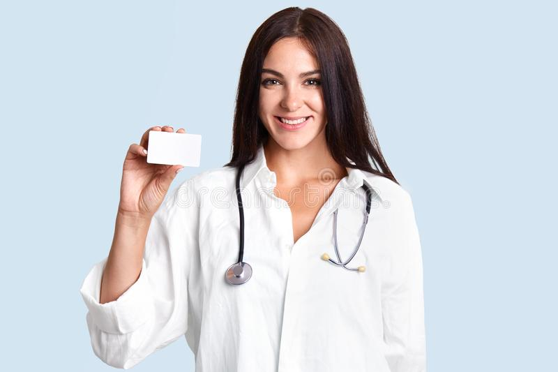 Красивый профессиональный женский терапевт носит белое медицинское пальто, стетоскоп, карточку владениями пустую, улыбки нежно, и стоковое фото
