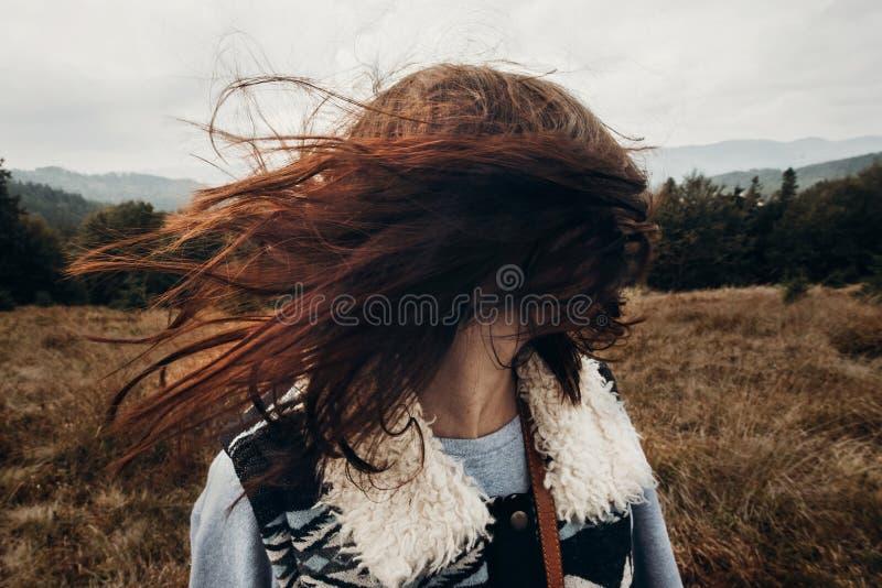 Красивый путешественник битника имея потеху в ветреных горах, playin стоковая фотография