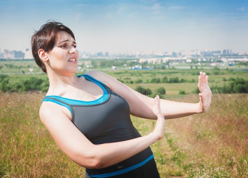 Красивый плюс женщина размера в sportswear делая выжимк показывать стоковое изображение