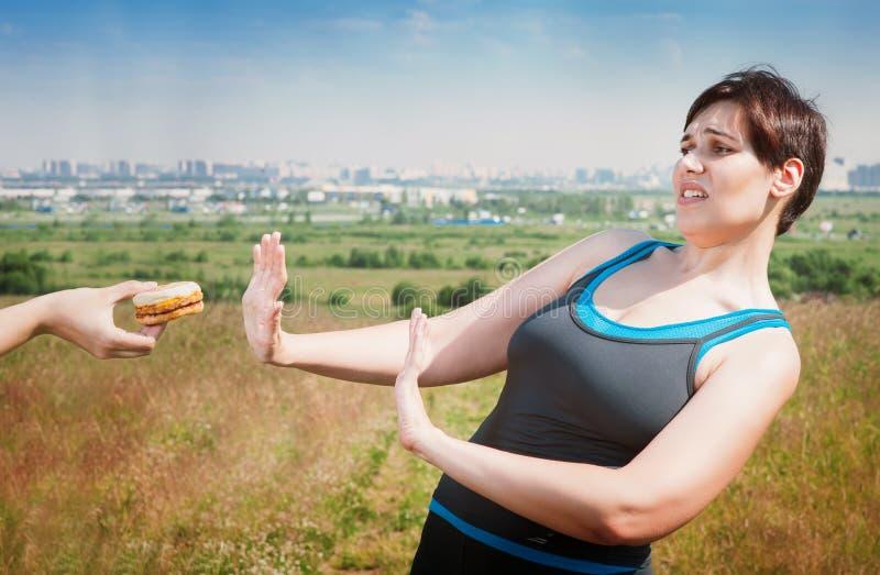 Красивый плюс женщина размера в sportswear отказывая высококалорийную вредную пищу стоковые изображения rf