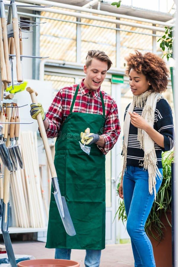 Красивый работник помогая клиенту с выбирать садовничая инструмент стоковое фото