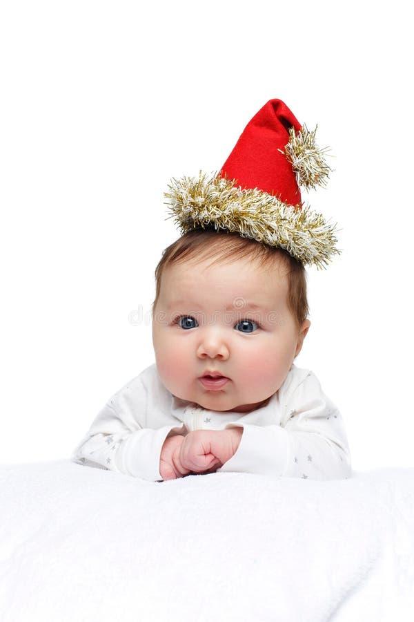 Красивый ребенок в шляпе рождества на белом одеяле стоковые фотографии rf