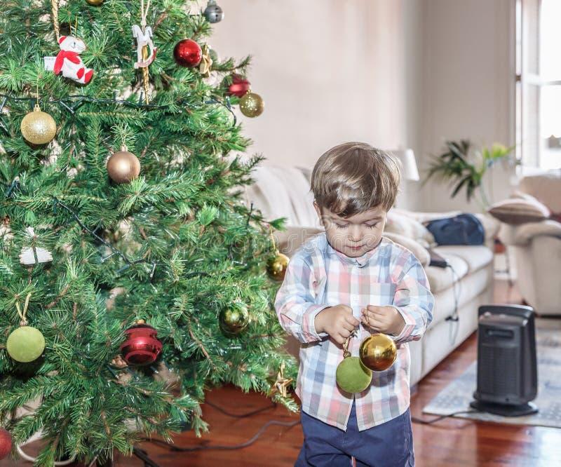 Красивый ребенок, игра с 2 покрашенными шариками рядом с рождественской елкой в живущей комнате стоковые фото