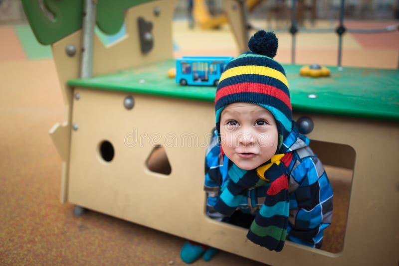 Красивый ребенок сидит в небольшом доме на районе спортивной площадки стоковые изображения