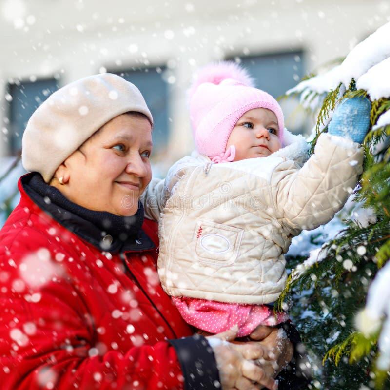 Красивый ребенок удерживания бабушки в pram во время снежностей в зиме E Беспечальное детство и стоковое изображение rf