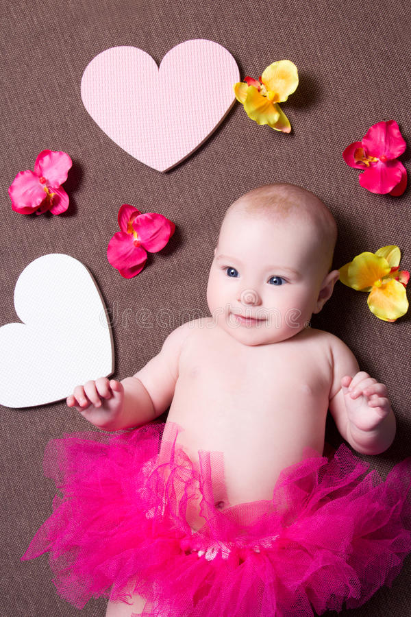 Красивый ребёнок в розовой юбке лежа с сердцами и цветками стоковая фотография rf