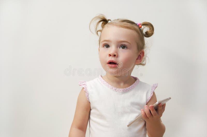 Красивый ребёнок играя и касаясь мобильный телефон стоковые фотографии rf