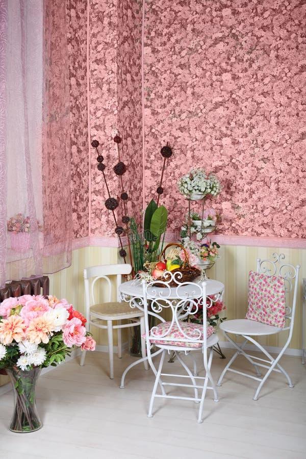 Красивый ретро интерьер с таблицей, стульями, розовыми обоями стоковые изображения