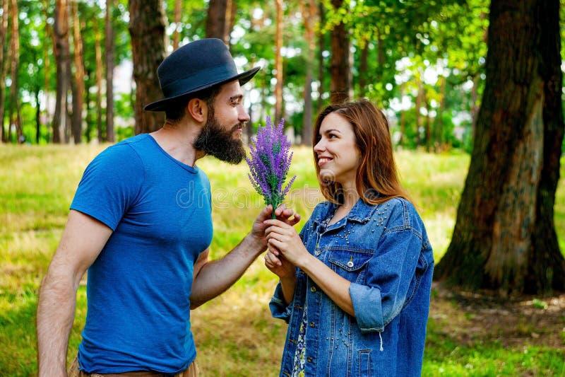 Красивый романтичный человек дает цветки его девушке стоковые изображения rf