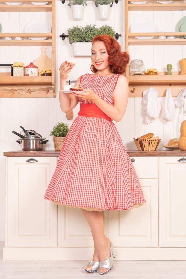 Красивый рыжеволосый pinup усмехаясь счастливо девушка представляя в ретро красном платье и белых высоких пятках стоковое изображение rf