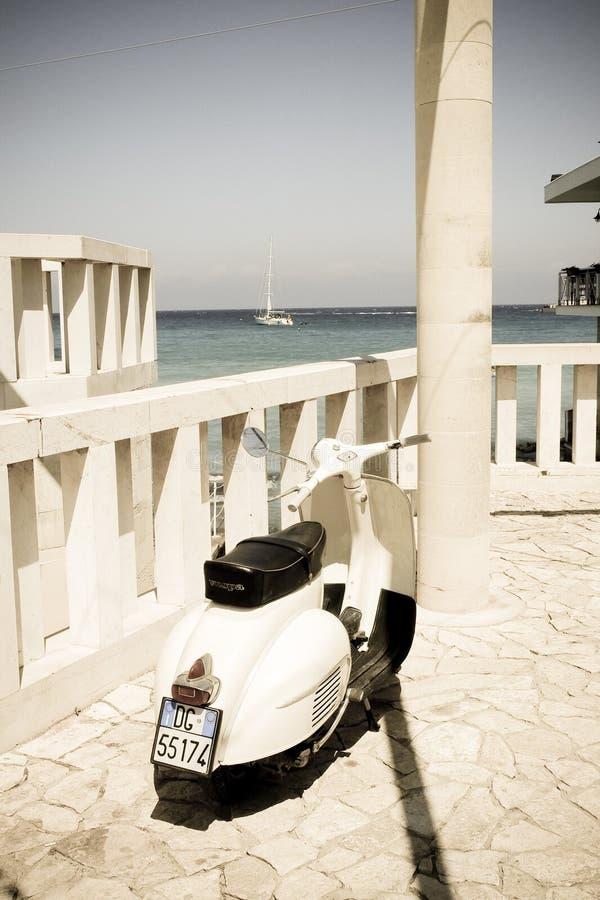 Красивый самокат Vespa в южном итальянском фильтре пляжа с стоковые изображения