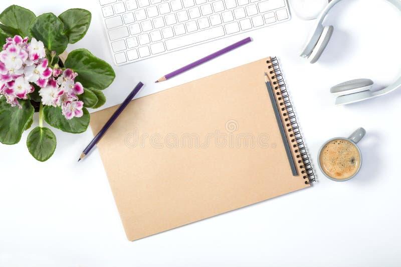 Красивый светлый модель-макет Белая современная клавиатура, наушники, канцелярские принадлежности, симпатичный цветочный горшок и стоковое фото