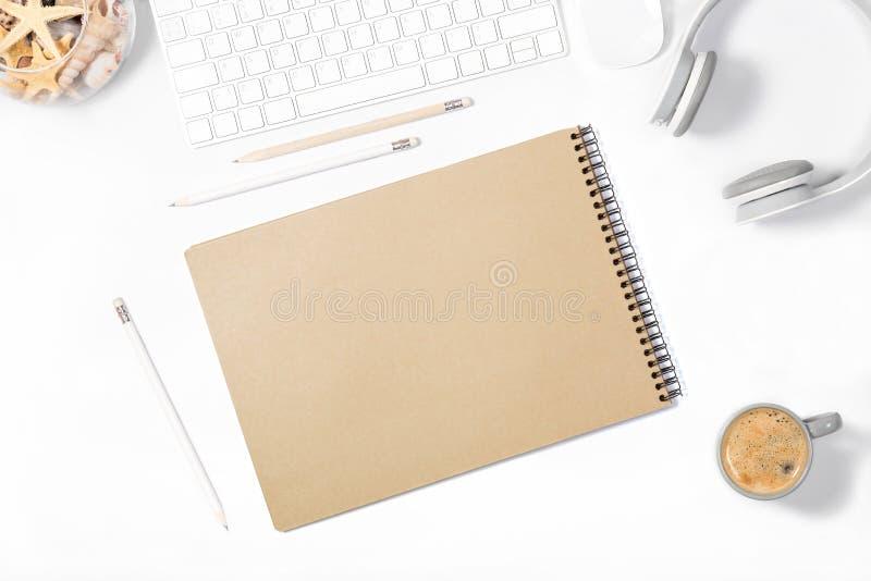 Красивый светлый minimalistic модель-макет Белая клавиатура, мышь, наушники, карандаши, sketchbook, ваза с seashells и чашка cofe стоковое изображение rf