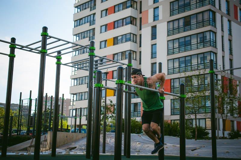 Красивый сексуальный мужской человек спортсмена культуриста делая разминку crossfit в атлетических объектах на солнечном утре out стоковое изображение rf