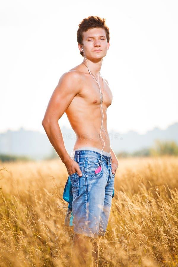 Красивый сексуальный мышечный человек представляя outdoors вне города в поле и слушая к музыке на наушниках стоковое изображение rf