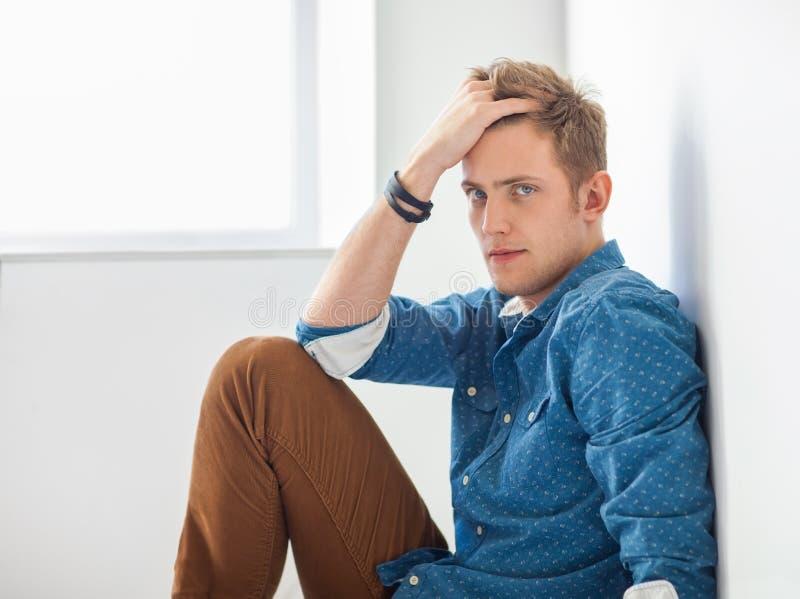 Красивый серьезный человек сидя на поле стоковое изображение rf
