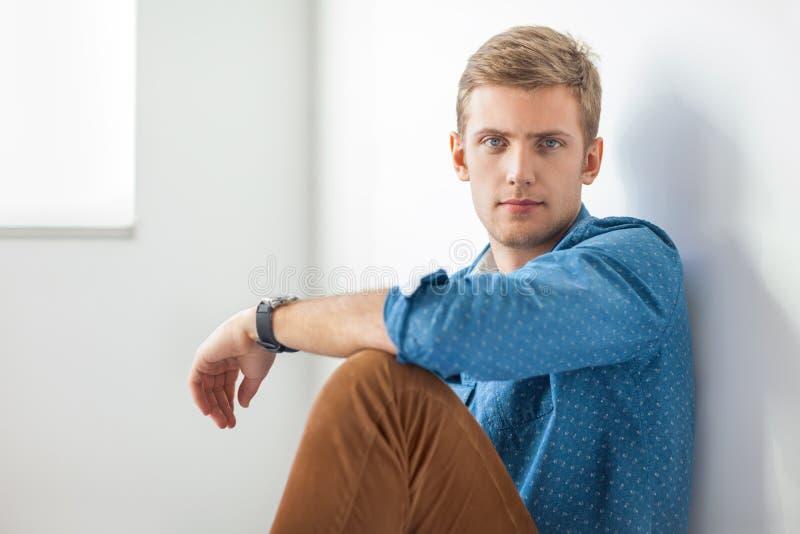 Красивый серьезный человек сидя на поле стоковое фото