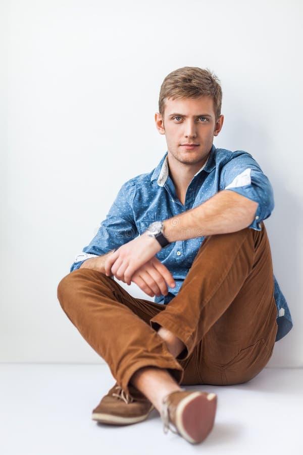 Красивый серьезный человек сидя на поле стоковые фотографии rf