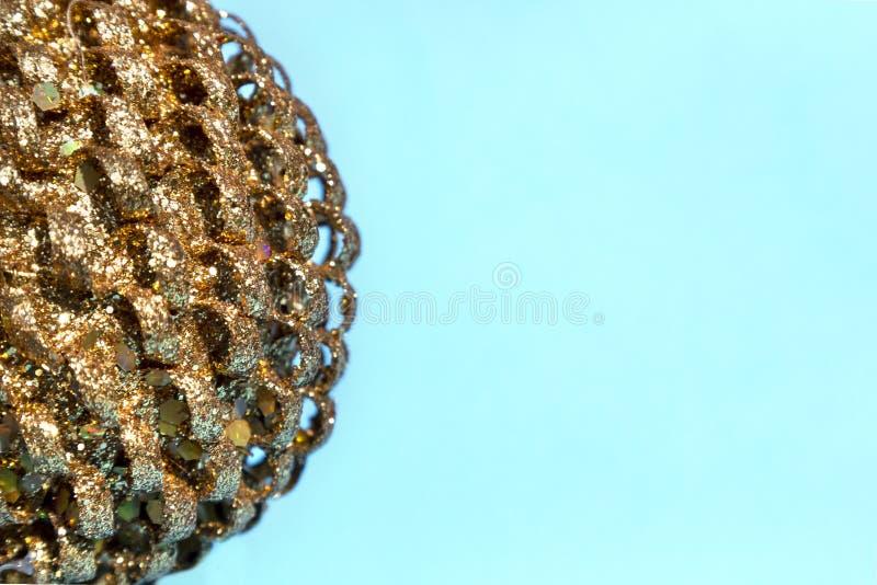 Красивый сияющий золотой шарик на голубой предпосылке Орнаменты рождества, Новый Год и концепция зимы стоковые фотографии rf