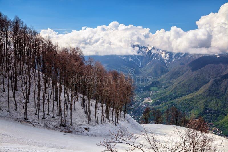 Красивый снежный наклон лыжи горы Aibga на пасмурную предпосылку голубого неба на ландшафте весны драматическом сценарном стоковое изображение rf