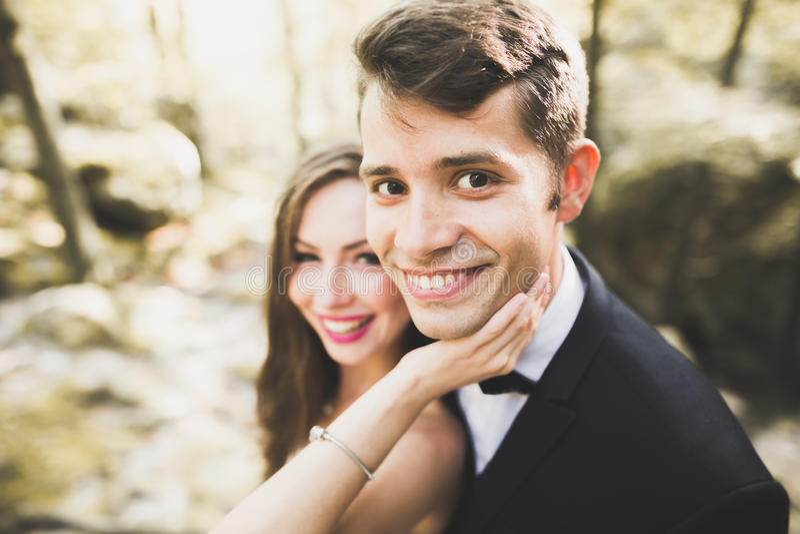 Красивый, совершенный счастливый жених и невеста представляя на их день свадьбы близкий портрет вверх стоковые изображения rf