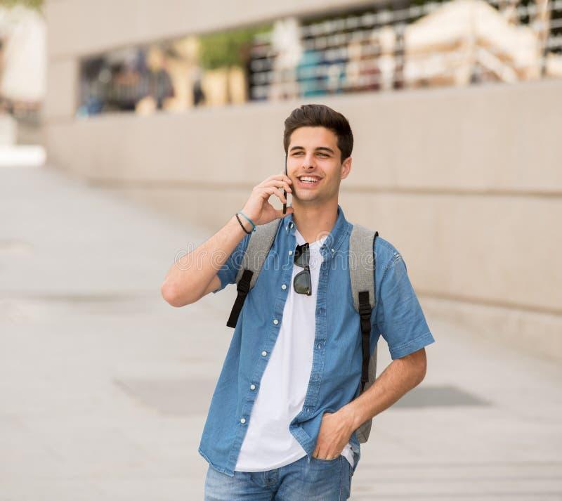 Красивый современный счастливый молодой человек говоря на его умном outsi телефона стоковая фотография