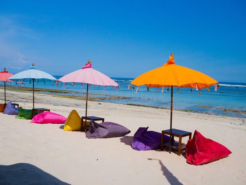 Красивый солнечный день с красочными зонтиками в ряд в пляже pandawa Pantai, в острове Бали, Индонезия стоковая фотография