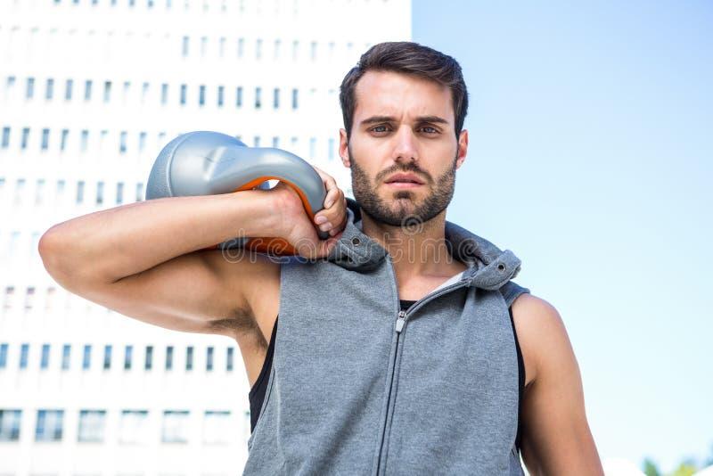 Красивый спортсмен держа колокол чайника стоковая фотография rf