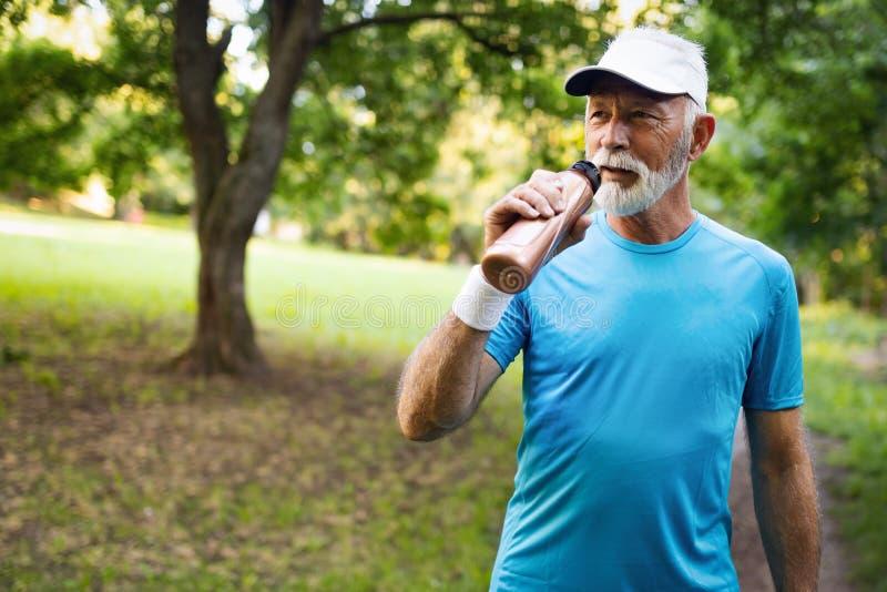 Красивый старший человек отдыхая после jog на парке на солнечный день стоковые изображения