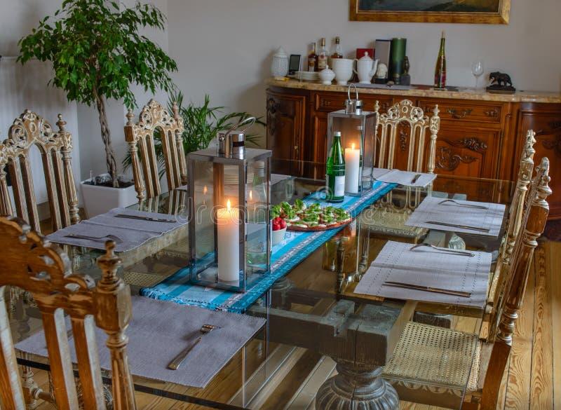 Красивый стеклянный стол с стульями еды и антиквариата в комнате с окном стоковое фото