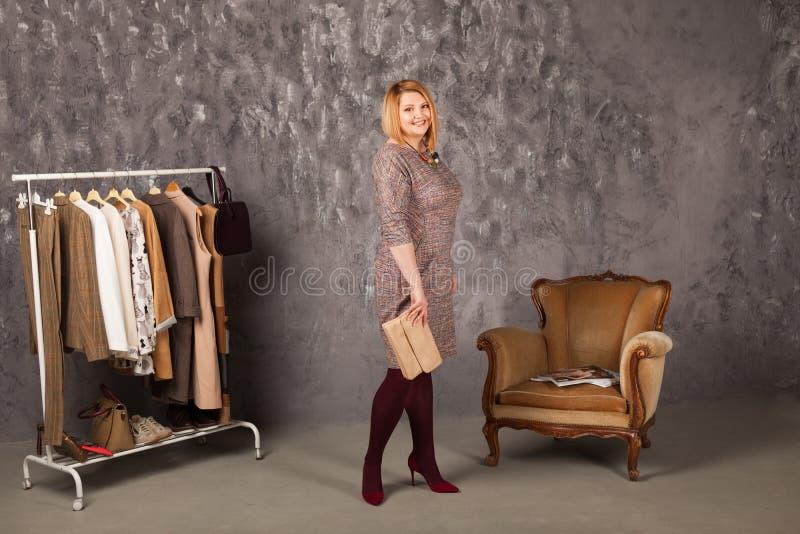 Красивый стилизатор около шкафа с вешалками стоковое изображение