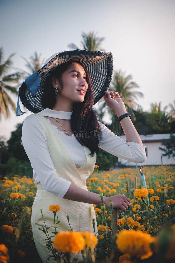 Красивый стиль Азии женщины на желтом sm цветочного сада и смотреть стоковое фото rf