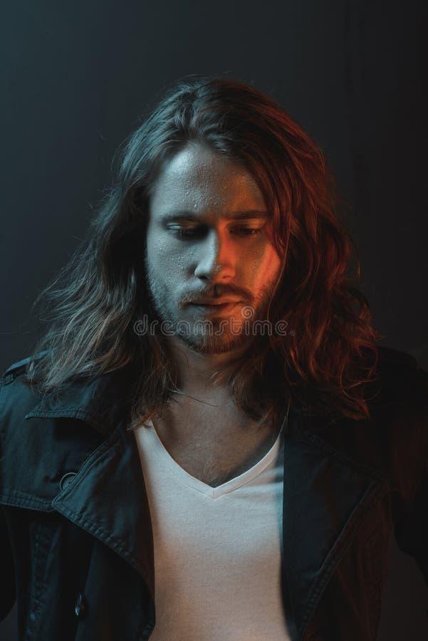 Красивый стильный бородатый молодой человек при длинные волосы смотря вниз в студии стоковое изображение rf