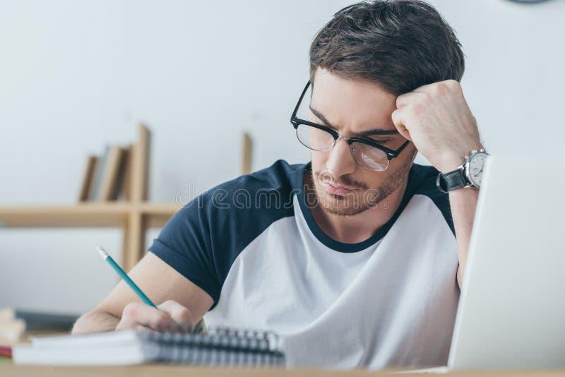 красивый студент в записи eyeglasses стоковая фотография rf