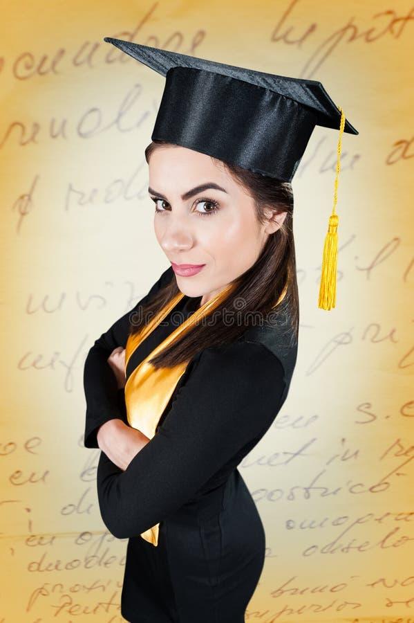 Красивый студент-выпускник женщины нося мантию градации стоковые изображения