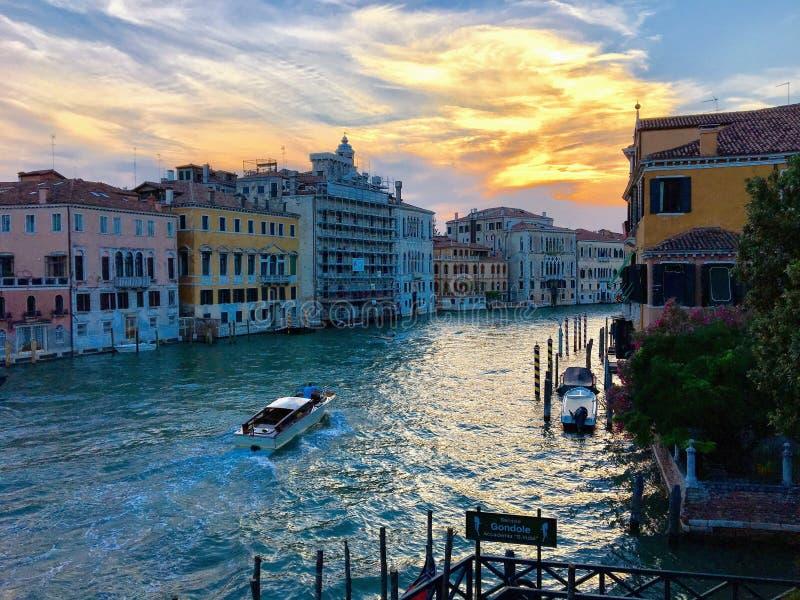 Красивый сценарный взгляд одиночной гребли такси воды вниз с большого канала как наборы солнца стоковое изображение