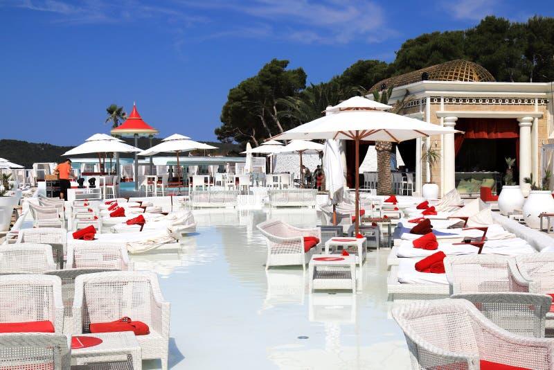 Красивый сценарный взгляд пляжа лета, бассейн края роскошный Белые deckchairs моды на пляже морем стоковое фото rf