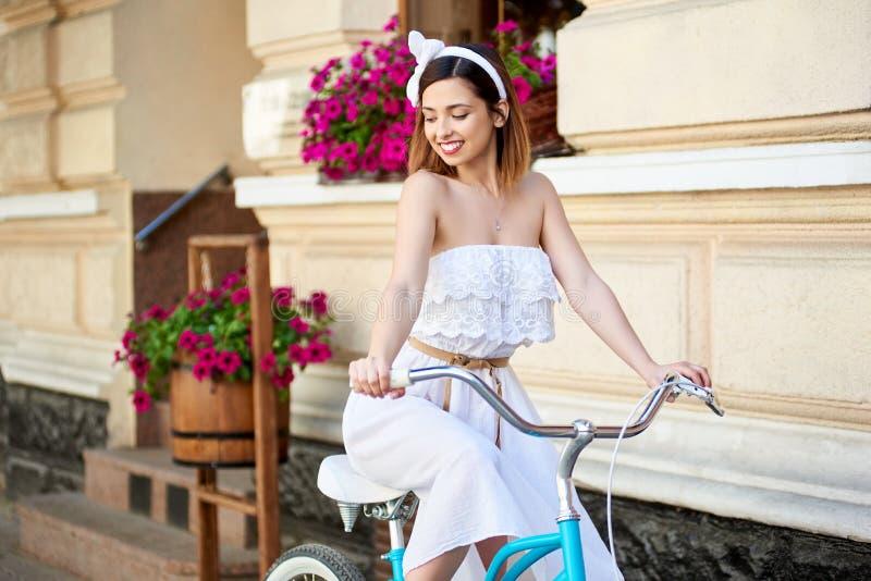 Красивый счастливый велосипед катания женщины в городе стоковое изображение rf