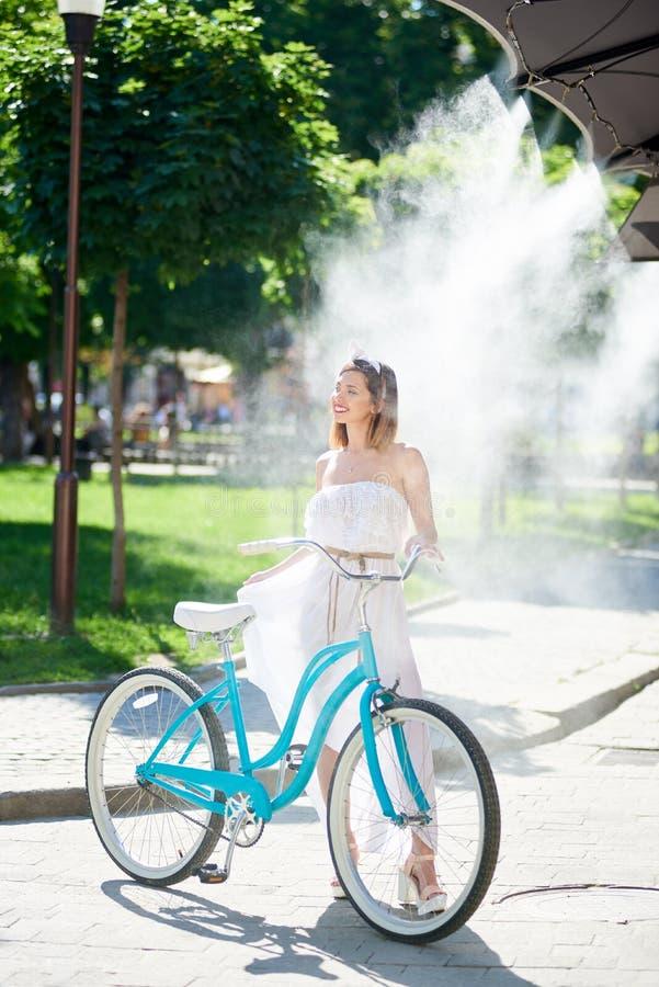 Красивый счастливый велосипед катания женщины в городе стоковые изображения