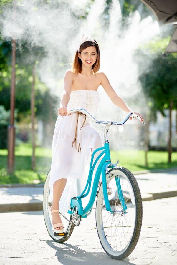 Красивый счастливый велосипед катания женщины в городе стоковые фотографии rf