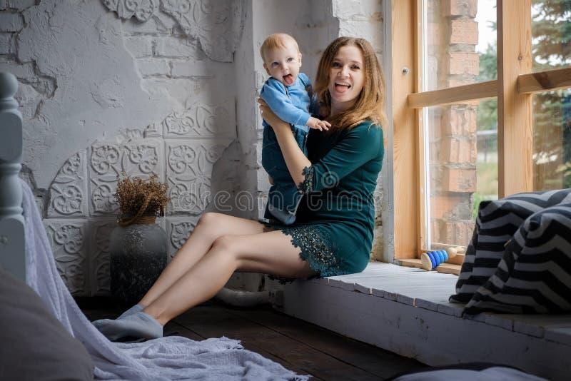 Красивый счастливый голубоглазый младенец сидя с ее матерью на windowsill Они смотрят камеру и показывают их язык стоковые изображения
