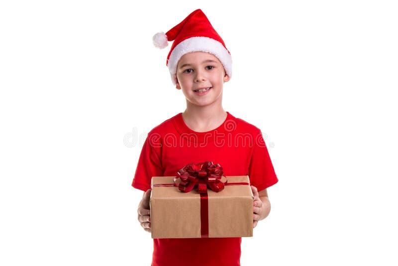 Красивый счастливый мальчик, шляпа santa на его голове, с подарочной коробкой в руках Концепция: рождество или С Новым Годом! пра стоковые изображения