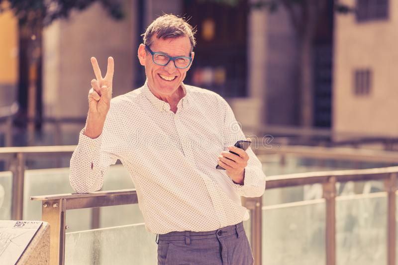 Красивый счастливый человек в его 60s отправляя и получая текстовые сообщения на его мобильном телефоне в старике используя социа стоковые изображения rf