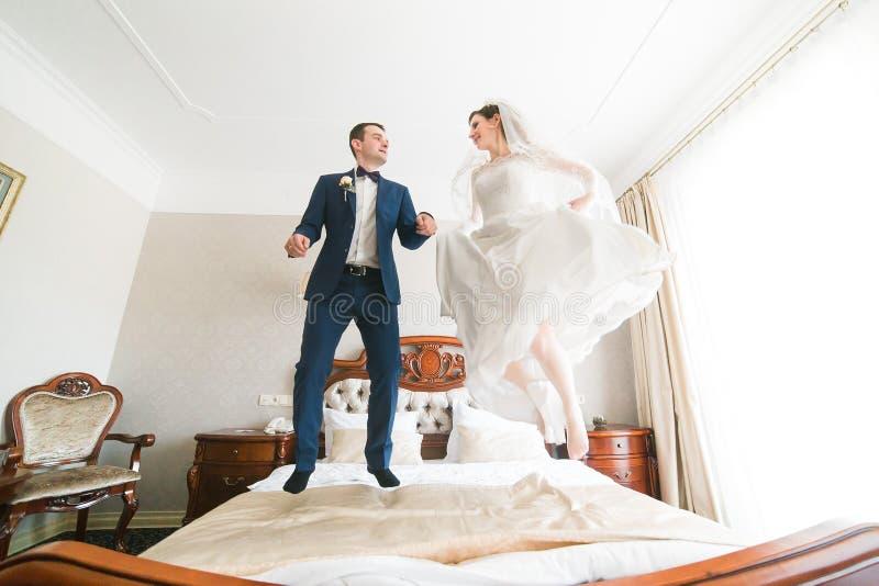 Красивый счастливый жених и невеста скача на кровать в богатом интерьере гостиницы стоковое фото