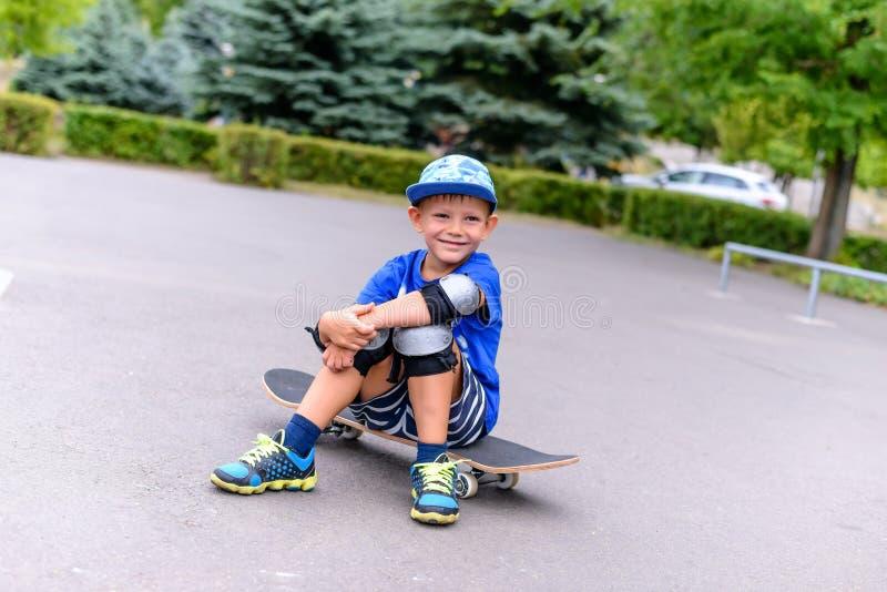Красивый счастливый молодой мальчик на его скейтборде стоковая фотография rf