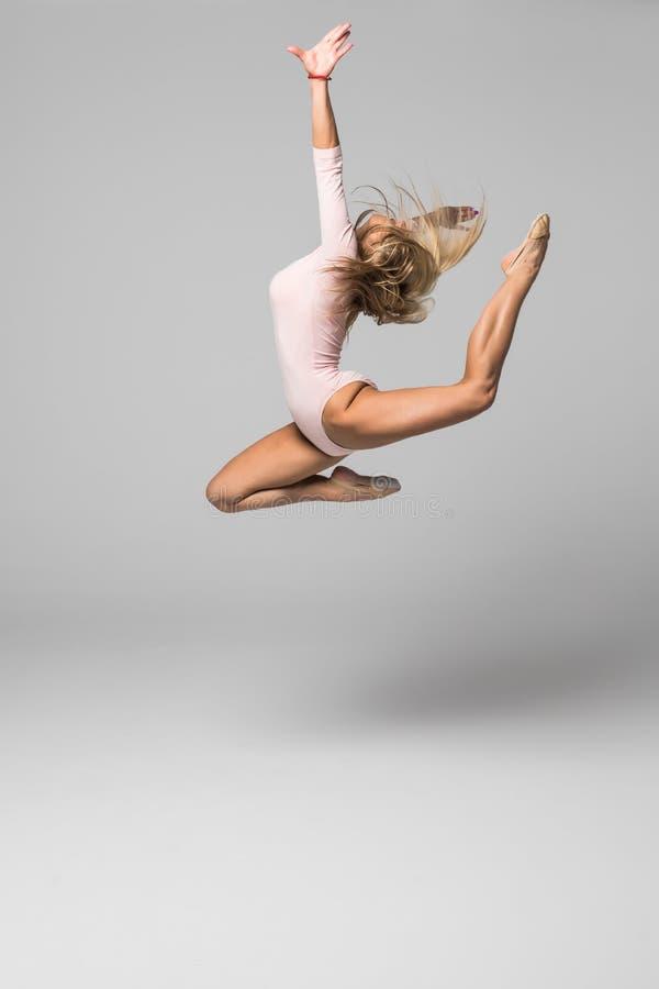 Красивый танцор женщины скачет с высокой ногой вверх на белой предпосылке стоковое фото rf