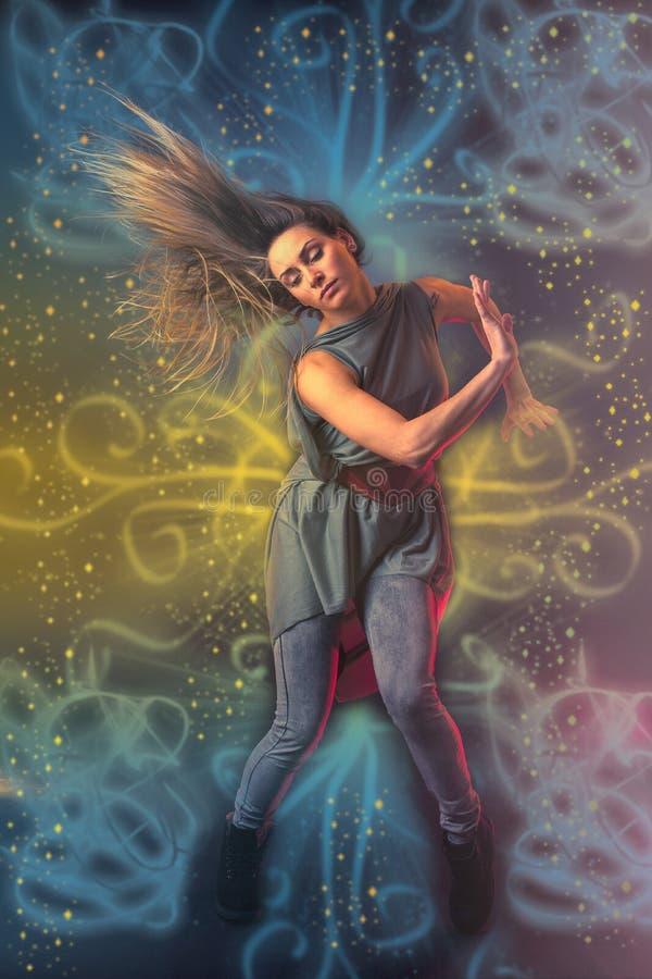 Красивый танцор женщины танцуя над темной предпосылкой с светом r стоковая фотография rf
