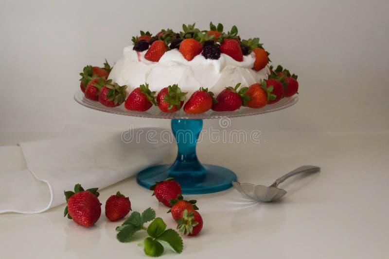 Красивый торт Pavlova сделанный из французской меренги, взбитой сливк, украшенной с клубникой стоковые фотографии rf