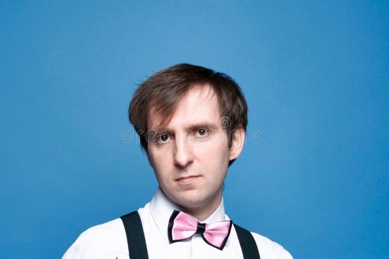 Красивый уверенный человек со светлыми волосами в розовой бабочке смотря камеру стоковое изображение rf