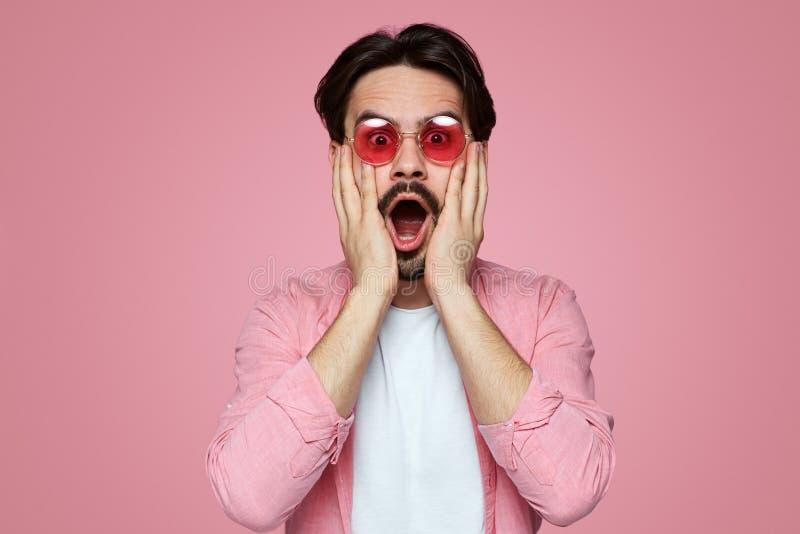 Красивый удивленный молодой мальчик касаясь бородатой стороне на розовой предпосылке стоковые изображения rf